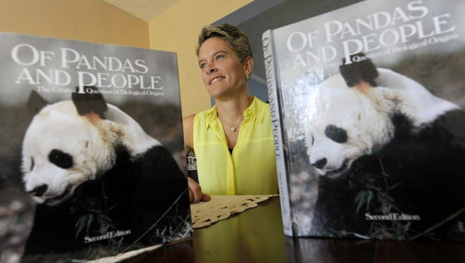 """Dover science teacher Jen Miller poses with her copies of the  """"Of Pandas And People"""" Intelligent Design books that she held onto from the time of the Dover High School court case."""