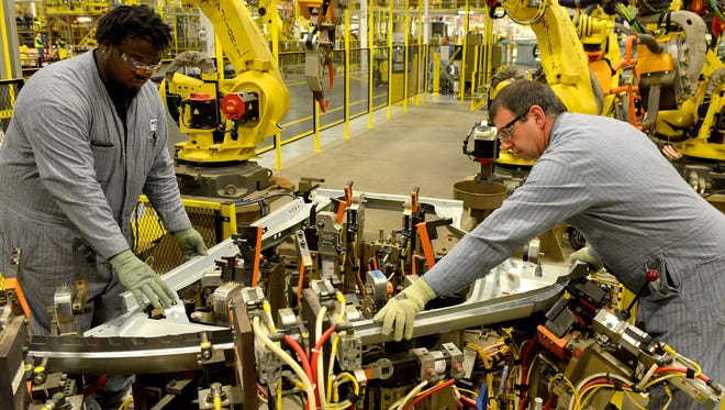 Jarvis Ford (left) and Joe Creason (right) work together on a right-hand door for the 2015 Ford Transit Van at Ford's Kansas City Assembly Plant.