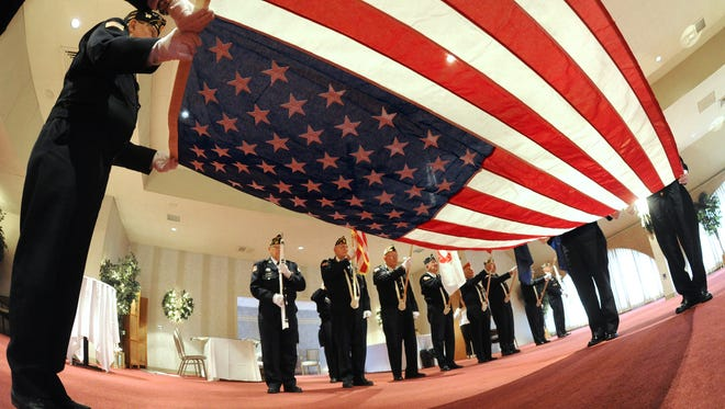 Members of the York County Veterans Honor Guard participate in the flag folding presentation during the Pearl Harbor/Battle of the Bulge remembrance ceremony in the White Rose Room at the York Expo Center in York, Pa., Friday, Dec. 6, 2013.