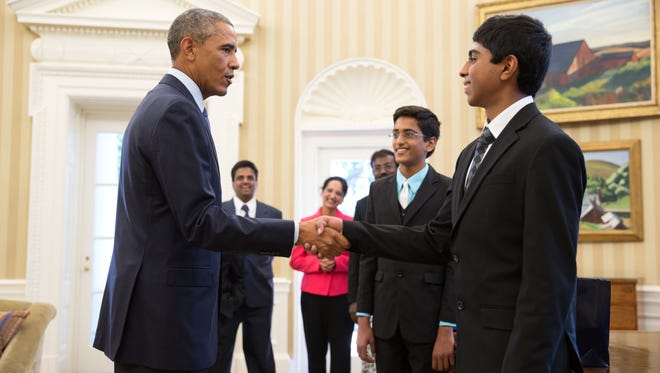 President Barack Obama shakes hands with Spelling Bee co-champion Ansun Sujoe of Forth Worth, Texas. Co-champion Sriram Hathwar of Painted Post is at Ansun's right. Sriram's parents are in the background.