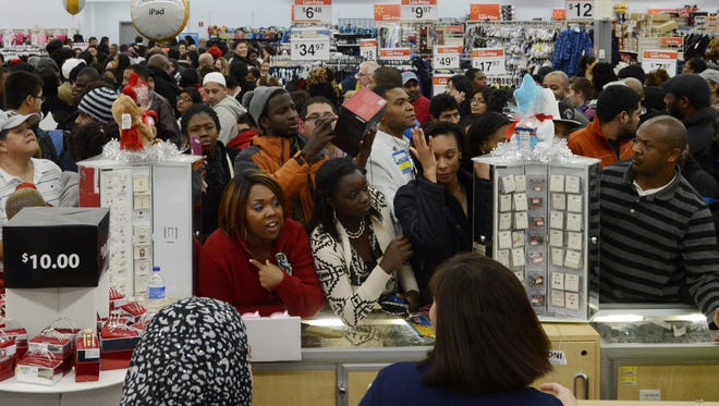 Crowds try to get the attention of employees  during a sale at a Walmart on Thanksgiving Day in Alexandria, Va.