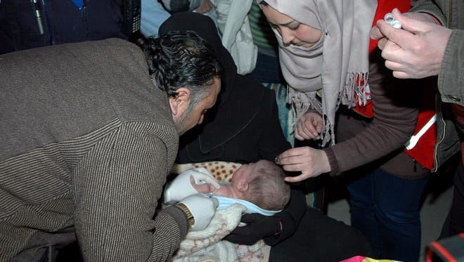 Syrian medics check a baby with a woman who was trapped in the rebels-held city of Homs.