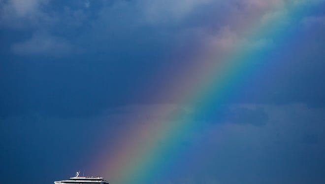 The Key West Express heads south on the Gulf of Mexico as it passes the base of a rainbow.