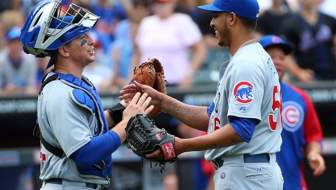 Chicago Cubs relief pitcher Hector Rondon catcher John Baker celebrate the win against the New York Mets at Citi Field. Chicago Cubs won 2-1.