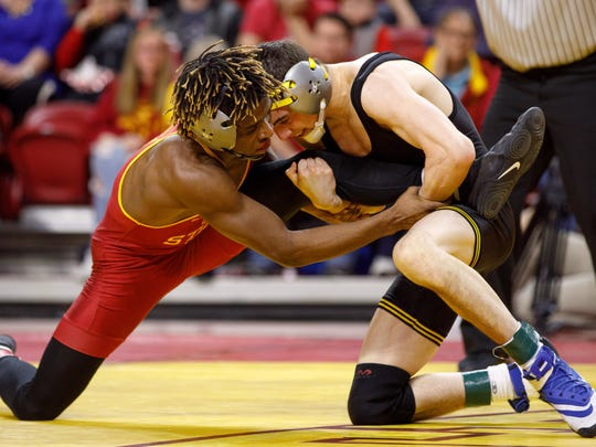 Iowa State University's Markus Simmons struggles against Iowa's Paul Glynn in the 133-pound match Sunday, Feb. 18, 2018, during their wrestling meet at the Hilton Coliseum in Ames.