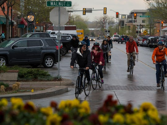 Cyclists cruise through the intersection of Linden Street and Walnut Street on Tuesday, May 1, 2018, in Fort Collins, Colo.