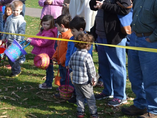 Children wait patiently behind yellow tape on Saturday