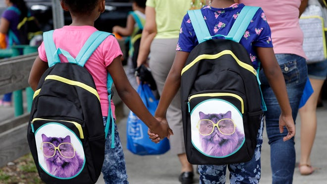 In this file photo, children in Miami hold hands as they walk with their new book bags.