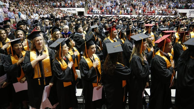 Graduates salute the flag during last year's summer commencement exercises at the University of Alabama's Coleman Coliseum on August 3, 2019 .