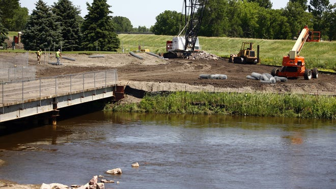 Men work near a temporary bridge crossing Skunk Creek near its entry into the Big Sioux River in 2010.