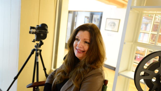Rebecca Courtney is photographed with her vintage movie making gear at the Reed Opera House in downtown Salem on Wednesday, Dec. 10, 2014. Courtney is property manager at the Reed Opera House.