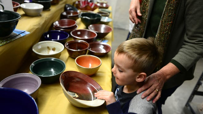 Ian Ludwig, 4, helped his grandmother, Peggy Haggerty, pick out handcrafted pottery during the Empty Bowls sale at the Willamette Art Center in November.