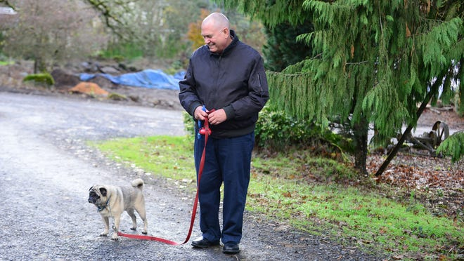 Dr. Peter Rasmussen takes his dog, Pugsley, for a walk around the East Salem neighborhood where he lives.