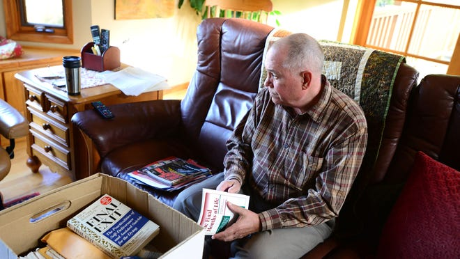 Dr. Peter Rasmussen, a retired medical oncologist who led the Death With Dignity movement and defended the Oregon law in the U.S. Supreme Court, looks through newspaper clippings and other files he kept during that time.