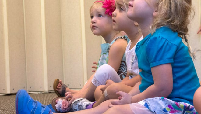 Aspen Yager, right, Cora Anderson, center, and Isla Lewis, left, quietly listen during story time at the Pace Library Friday morning.
