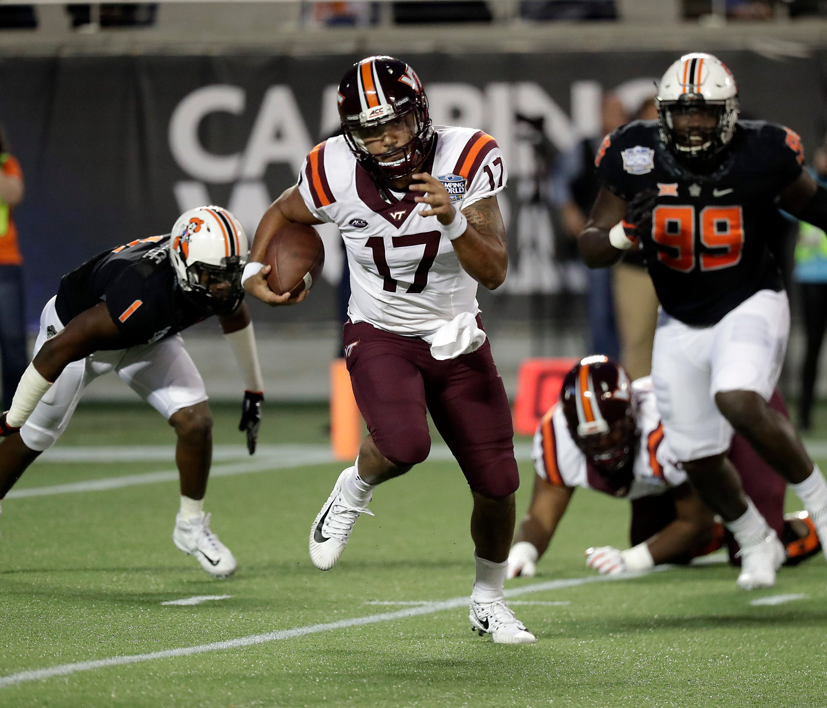 Virginia Tech quarterback Josh Jackson (17) scrambles away from Oklahoma State linebacker Calvin Bundage (1) and defensive end Trey Carter (99) during the first half of the Camping World Bowl NCAA college football game, Thursday, Dec. 28, 2017, in Or