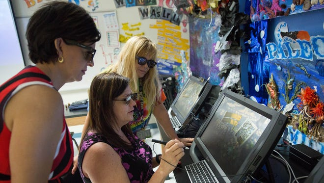 Dee Dickens, center, a professional services provider with zSpace, demonstrates the zSpace 300 3D computer consoles to Margarita Porter, left, principal of New America School and Patricia Dahlin-Dunne, right, a science teacher at the school. Friday, July 28,2017.