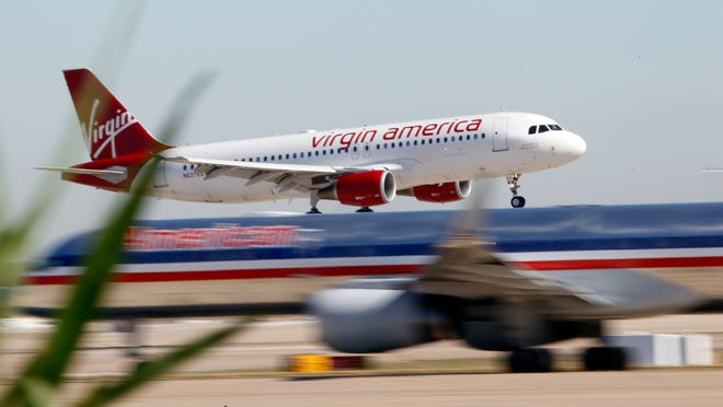 Virgin America's inaugural flight between Los Angeles and Dallas/Fort Worth lands within view of an American Airlines jet on Dec. 1, 2010.