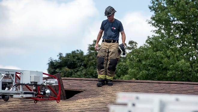 A firefighter with United Hook and Ladder looks into a hole which was cut into the roof of a home to help ventilate smoke, Sunday, July 16, 2017. The fire started in the kitchen area and took crews about 15 minutes to extinguish.
