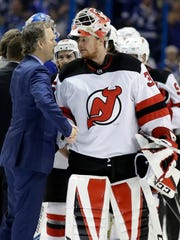 New Jersey Devils goaltender Cory Schneider, right, congratulates Tampa Bay Lightning head coach Jon Cooper after they eliminated the Devils during Game 5 of an NHL first-round hockey playoff series Saturday, April 21, 2018, in Tampa, Fla.