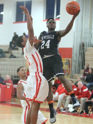 New Rochelle's Jamel Wallace drives to the basket against North Rockland's Jose Diaz during their game at North Rockland on Friday. New Rochelle won 47-43.