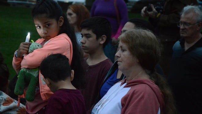 Eliciana Romano, 6, holds a candle as about 100 people gathered Wednesday for a vigil for victims of a traffic crash.