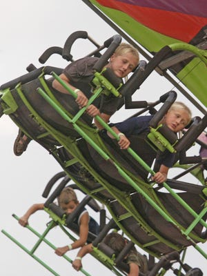 Youngsters hang on a ride at the Sheboygan County Fair.