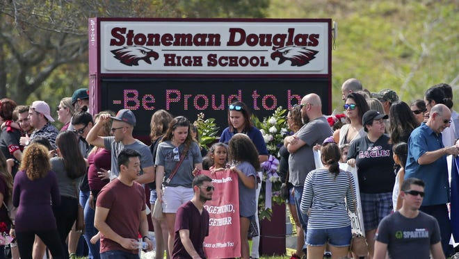 Parents and students arrive at Marjory Stoneman Douglas High School for an open house on Sunday, Feb. 25, 2018, in Parkland, Fla., as parents and students returned to the school for the first time since over a dozen were killed on Feb. 14.