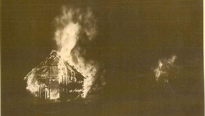 Photograph looking in the north entrance early in the 1935 fire at the CCC camp in Waterbury. The flames in the distance are at opposite end of the 160' x 180' building.