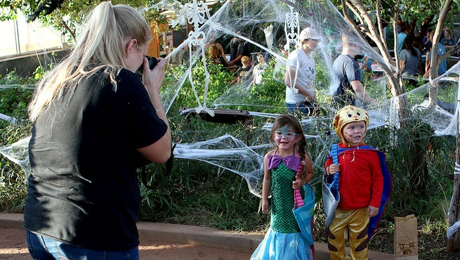Two children pose for photos in the Ruby N. Priddy Butterfly and Nature Conservatory at River Bend Nature Center's Not So Scary Halloween Friday evening.