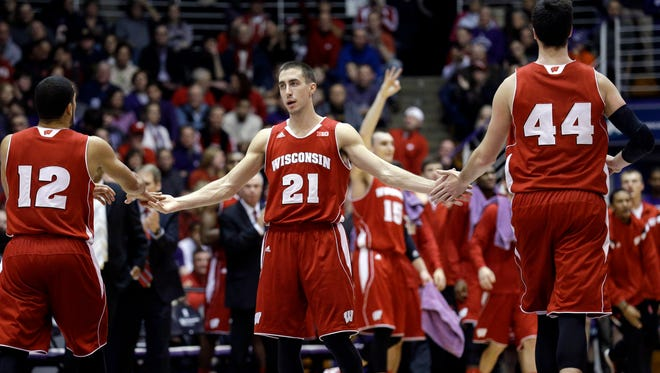 Wisconsin guard Josh Gasser (21) celebrates with guard Traevon Jackson (12) and forward Frank Kaminsky (44) after Duje Dukan (13) scored a basket during the first half against Northwestern.