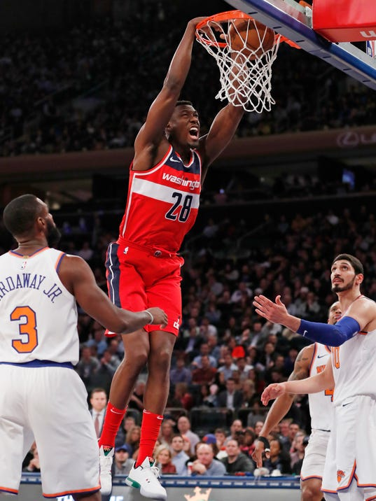 Washington Wizards center Ian Mahinmi (28) dunks as New York Knicks forward Tim Hardaway Jr. (3) and New York Knicks center Enes Kanter (00) watch from the floor in the first half of an NBA basketball game in New York, Wednesday, Feb. 14, 2018. (AP Photo/Kathy Willens)