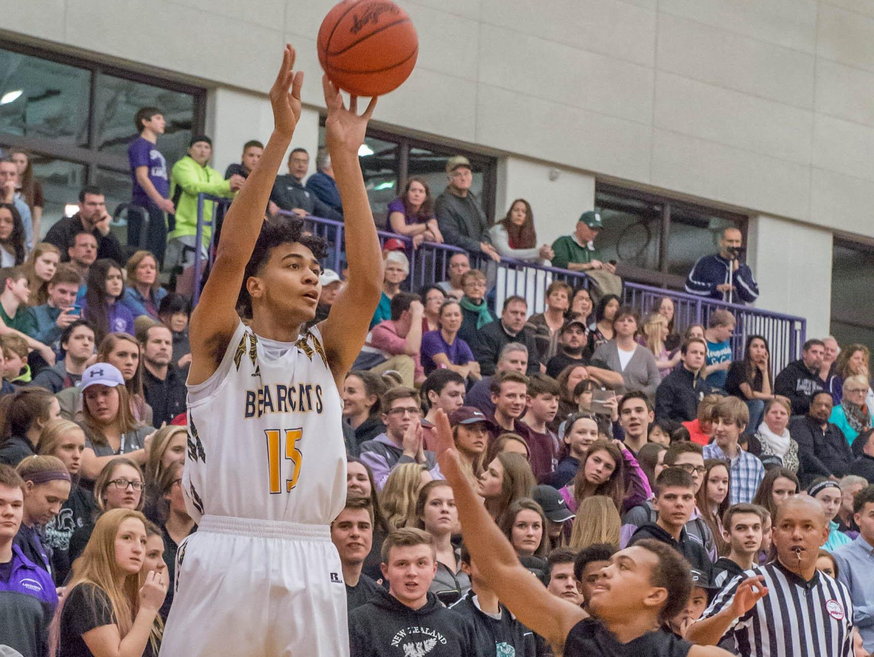 Battle Creek Central's Austin Johnson (15) takes a shot over Lakeview's CJ Foster (12) during this city rivalry game last Friday.