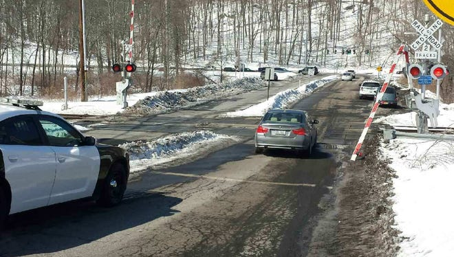 An arm for safety gates at the Roaring Brook Road crossing were broken by a motorist who became stuck on the tracks Saturday morning.
