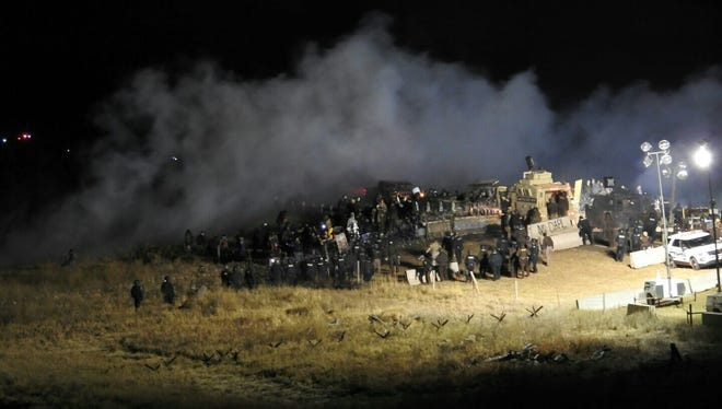 In this image provided by Morton County Sheriff's Department, law enforcement and protesters clash near the site of the Dakota Access pipeline on Sunday, Nov. 20, 2016, in Cannon Ball, N.D. The clash came as protesters sought to push past a bridge on a state highway that had been blockaded since late October, according to the Morton County Sheriff's Office. (Morton County Sheriff's Department via AP)