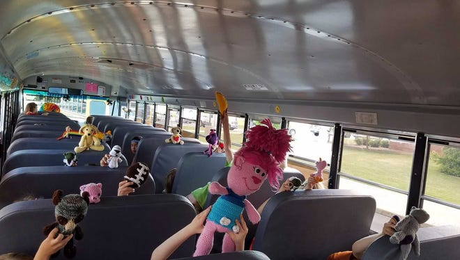 Children show off stuffed toys made for each of them by Oconomowoc Transport Co. bus driver Trudy Serres.