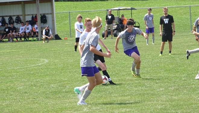 Watkins Memorial junior Simon Blum attempts to slip between two Logan defenders during a recent scrimmage.