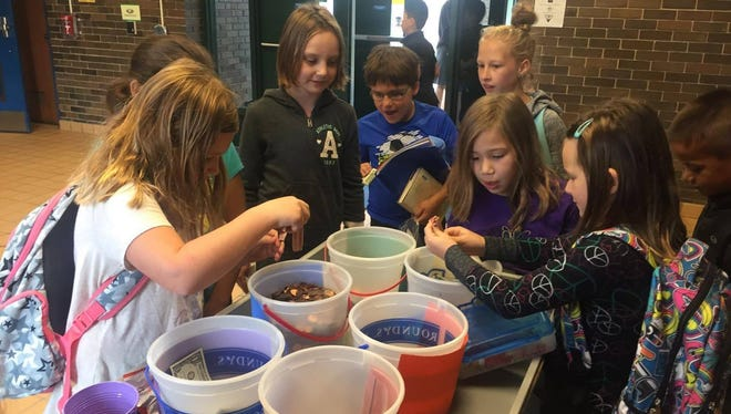 Elementary students plop in their donations of change into buckets at College Park Elementary for the Penny War fundraiser. The school collected donations from Oct. 3-6.