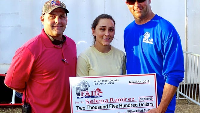 Firefighters' Indian River County Fair General Manager Wayne Howard, left, and Vero Beach Firefighters Association President Will Willmot, right, present a check for $2,500 to burn victim Selena Ramirez from the Indian River Burn Fund.