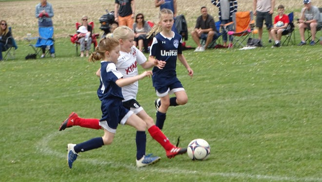 Emma Treece, of XTABI U9, attempts to split the Worthington United Academy defenders Sunday during a Buckeye Cup match at Alford-Reese Park.