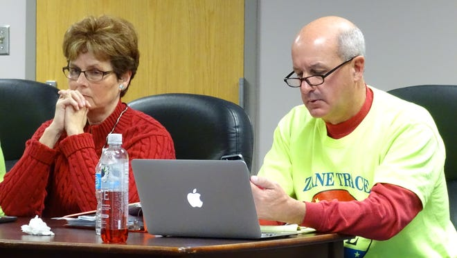 Zane Trace board member Cathy Chester listens as Superintendent Jerry Mowery reads precinct results for the district's earned income tax levy from a text message on his phone.