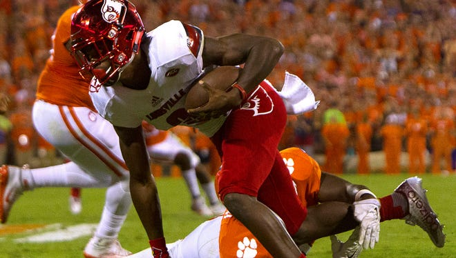 Clemson Tigers linebacker Kendall Joseph (34) attempts to bringdown Louisville Cardinals quarterback Lamar Jackson (8) during the second quarter at Clemson Memorial Stadium.