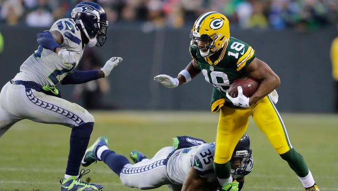 Packers wide receiver Randall Cobb (right) is brought down by the Seahawks' Jeremy Lane and DeShawn Shead during Sunday's game at Lambeau Field in Green Bay.