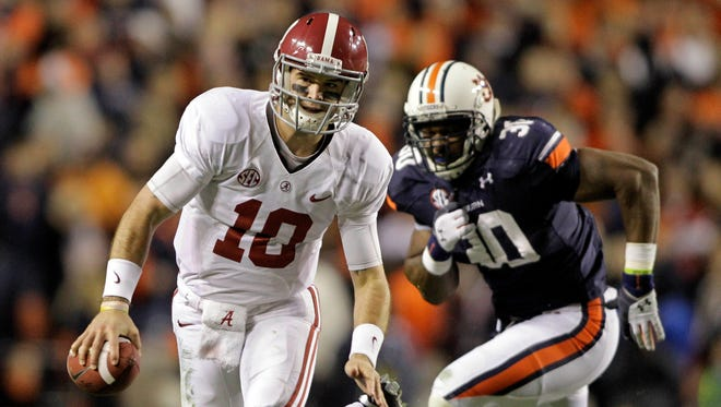 Alabama quarterback AJ McCarron (10) scrambles away from Auburn defensive end Dee Ford (30) during the fourth quarter on Nov. 30 at Jordan-Hare Stadium. If the teams met again, according to analyst Jeff Sagarin, Alabama would be favored.
