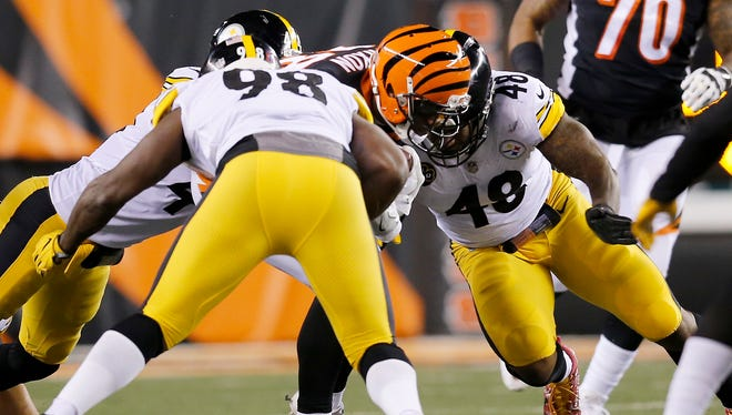 Pittsburgh Steelers outside linebacker Bud Dupree (48) makes helmet-to-helmet contact with Cincinnati Bengals running back Joe Mixon (28) on a run, causing him to leave the game, in the second quarter of the NFL Week 13 game between the Cincinnati Bengals and the Pittsburgh Steelers at Paul Brown Stadium in downtown Cincinnati on Monday, Dec. 4, 2017.