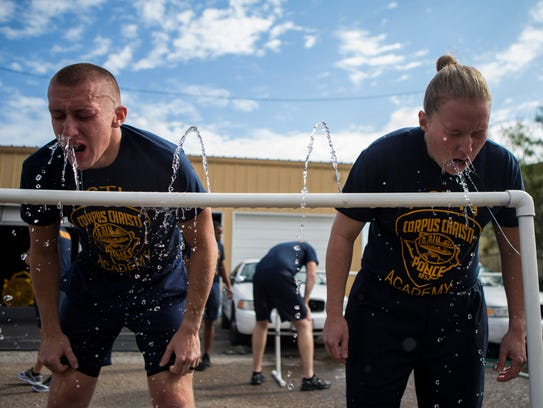 Police cadets wash off their faces after being exposed
