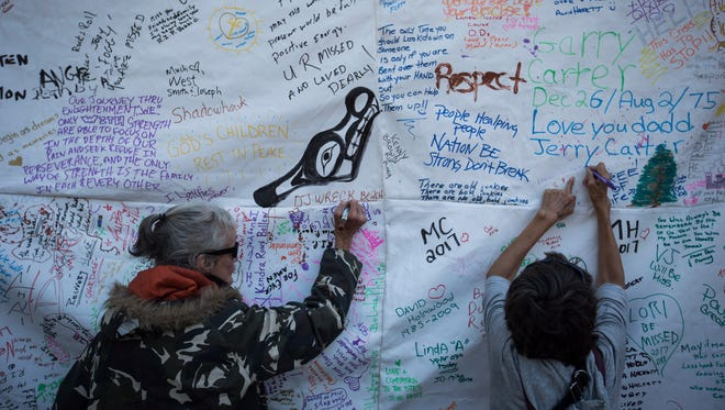 Women write messages on a banner during a memorial service to remember those who have died in the province as a result of the drug overdose crisis, on International Overdose Awareness Day in the Downtown Eastside of Vancouver, British Columbia, on Thursday, Aug. 31, 2017.