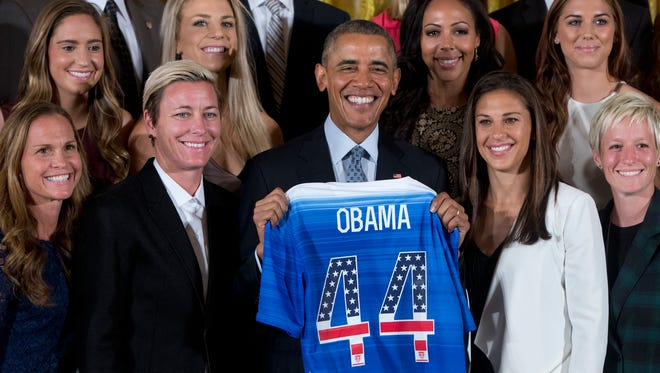 President Barack Obama poses for photos with a jersey he received from head coach Jill Ellis as he welcomed the U.S. Women's National Soccer Team, Tuesday, Oct. 27, 2015, in the East Room of the White House in Washington during a ceremony to honor the team and their victory in the 2015 FIFA Women's World Cup. Standing with Obama, from left are, Christie Rampone, Morgan Brian, Abby Wambach, Julie Johnston, Obama, Sydney Leroux, and Carli Lloyd, Alex Morgan, and Megan Rapinoe.