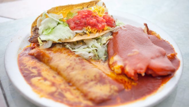 A plate with a cheese enchalada (L), a machaca taco (top) and a tamale (R) sit on a table at La Perla Cafe.