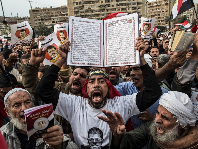 A man holds up a Quran as supporters of Egyptian President Mohammed Morsi and members of the Muslim Brotherhood chant slogans during a rally on Dec. 14, 2012, in Cairo.  Opponents and supporters of Morsi staged rallies before a referendum vote on the country's draft constitution that was rushed through parliament in an overnight session on Nov. 29.